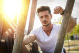 Attractive man in urban setting in front of big metal structure