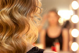 Close up of curly hair and blurred reflection of hairdresser making curls in beauty salon. - 190157285