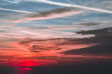 Tinted sunset ,sunrise sky with plane avia trails and leads, orange, red  and blue fantastic clouds, amazing colours . City town photo concept and relax, wallpaper background . Copy space photo  .