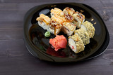 Fototapeta Maki - Sushi rolls with ginger and wasabi on a black plate © Alexspdz