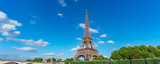 The Eiffel Tower panorama over trees, blue sky