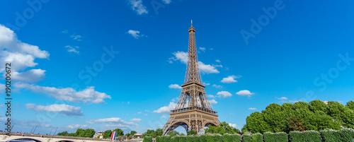 Tuinposter Eiffeltoren The Eiffel Tower panorama over trees, blue sky