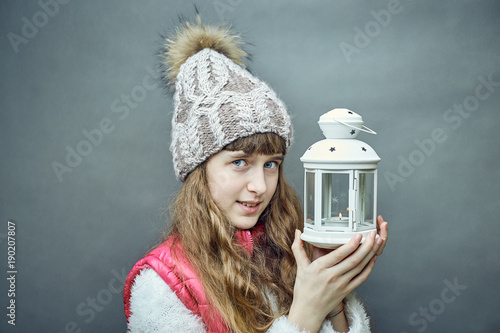 Girl with a white lamp in hands on a gray background. © trek6500