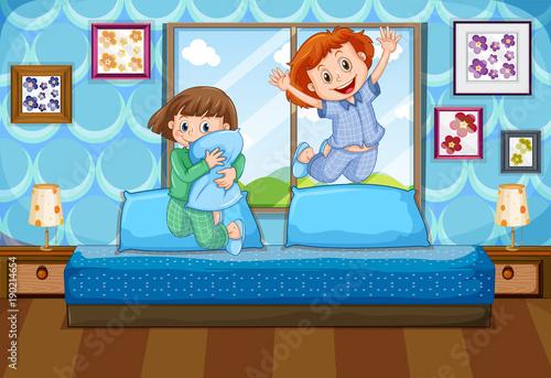 Keuken foto achterwand Kids Two girls in pajamas jumping on bed