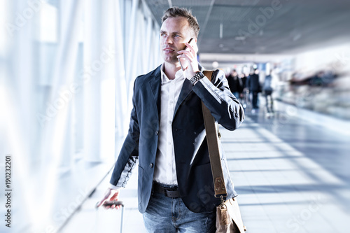 Businessman talking on phone in airport