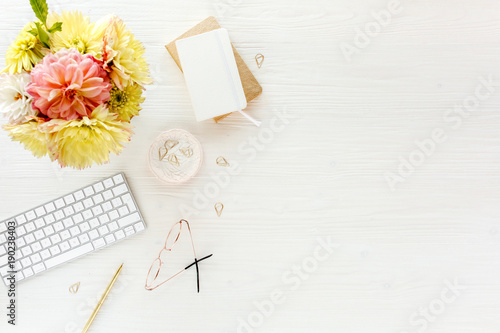 Flat lay women's office desk. Female workspace with pink and yellow dahlias and roses flowers bouquet, accessories, golden diary, glasses on white wooden