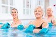 Leinwandbild Motiv People young and senior in water gymnastics physiotherapy with dumbbells