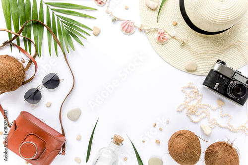 Feminine beige swimsuit beach accessories, tropical palm leaf branches, coconuts on white background with empty space for text. Summer background. Traveler accessories. Flat lay, top view.