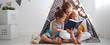 Leinwandbild Motiv family mother reading to children book in tent at home
