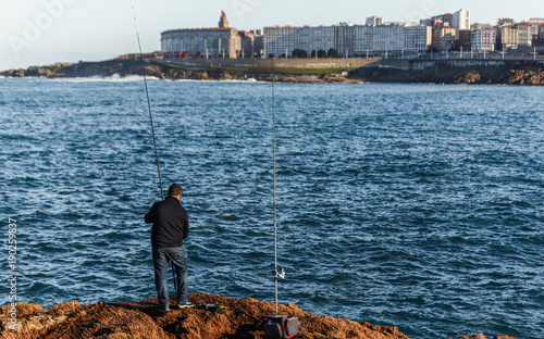 "Fisherman from behind and the ""Hercules Tower"" in the background"