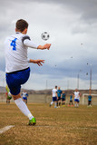 Football player on field kicks the soccerball during soccer match. Blur team, sky for background.