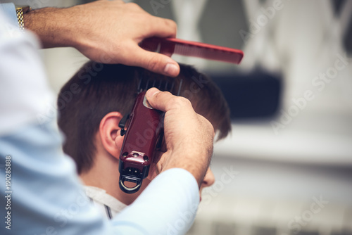 Barber is doing haircut to Caucasian boy using hair clipper in barbershop.