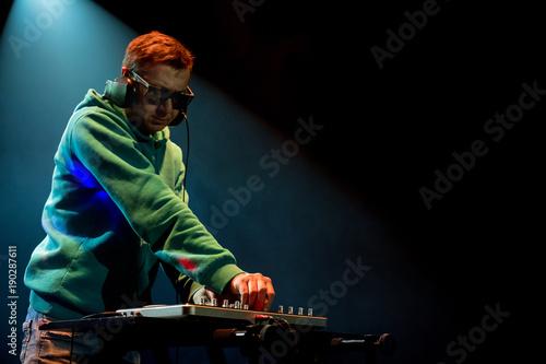 Fotobehang Muziek DJ work in a nightclub. Disco light in the club. DJ behind the turntable.