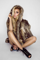 Beautiful, sexy naked blond model, dressed only in elegant fur.