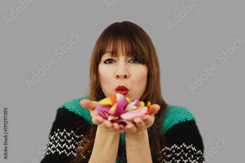 Frau vor grauem Hintergrund pustet Blütenblätter