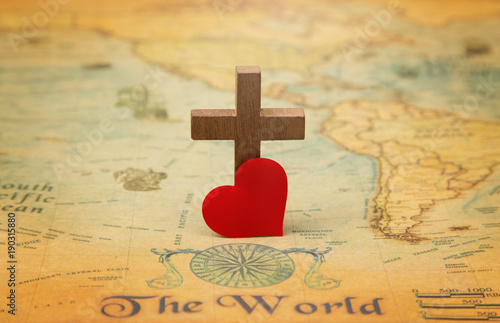 Fototapeta For God so loved the world - A Cross on a rustic world map