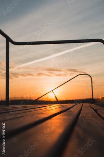 Fotobehang Chocoladebruin Blurred Sunset with Focus on Boardwalk