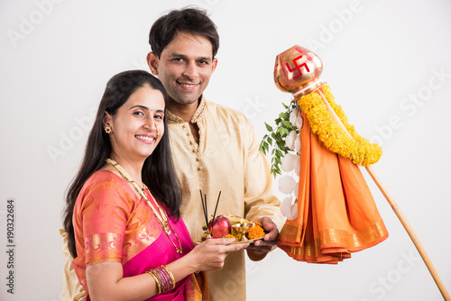 Foto Murales portrait of happy indian couple standing with puja or pooja thali doing gudi padwa or gudhi padwa poojan, asian couple and gudi padwa celebration, hindu new year celebration, isolated on yellow