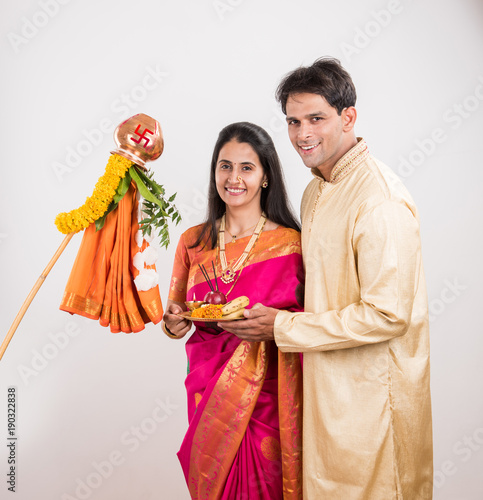 portrait of happy indian couple standing with puja or pooja thali doing gudi padwa or gudhi padwa poojan, asian couple and gudi padwa celebration, hindu new year celebration, isolated on yellow