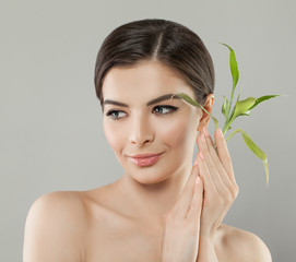 Attractive Woman with Green Bamboo Leaves. Beautiful Young Spa Model with Healthy Skin