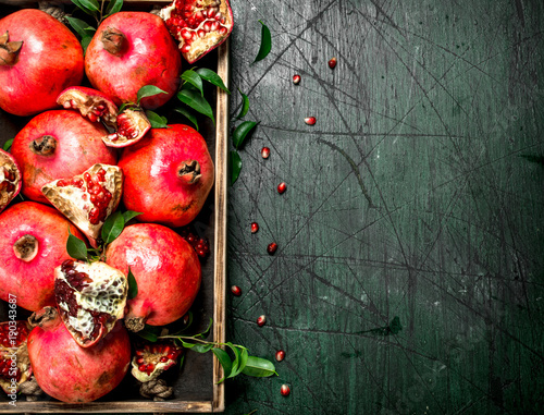 Foto Murales Fresh pomegranates on a wooden tray.