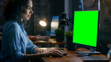 Beautiful Female Office Employee at Her Desk Works on a Mock-up Green Screen Personal Computer. Her Colleague Sits Beside. Creative Office Evening. - 190345425