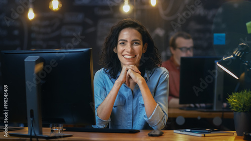 Beautiful Female Office Employee Works at Her Desk on a Personal Computer, She Interrupts Her Work and Smiles Charmingly for the Camera. In the Background  Coworker in the Creative Office.
