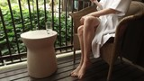 beautiful woman in a bathrobe drinking water sitting on the balcony - 190346067