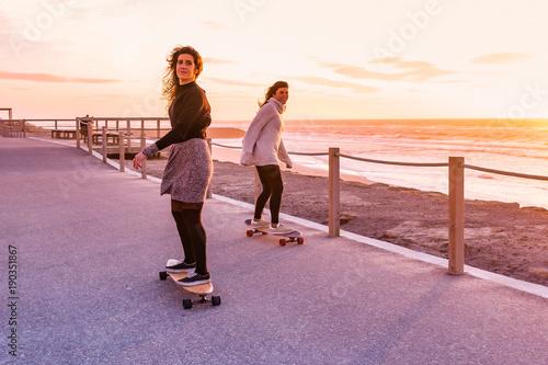 Fotobehang Skateboard Two female friends playing with skateboard