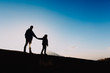 Quadro Silhouettes of father and son hiking at sunset