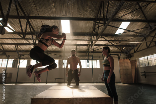 Woman jumping on wooden box guided by trainer