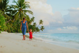 mother and cute little daughter walk on beach