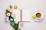 White desk with colorful macaroons, flowers, notebook, laptop and cup of coffee