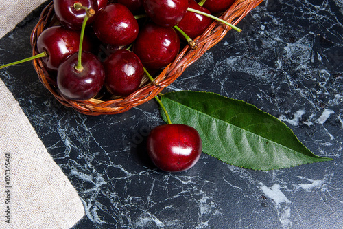 Fotobehang Kersen Several red sweet cherries and big green leaf on the table. Fresh organic cherry in yellow wooden basket on dark marble background..