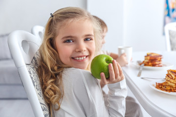 adorable little child with green apple looking at camera while having breakfast with family