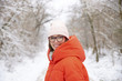 Woman taks a trip winter. Close-up shot of happy mature woman with hat standing outdoor in snowy landscape and looking at camera.