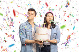 Teenagers with a birthday cake and party horns - 190390200
