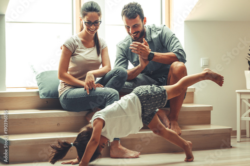Mother and father hangout with they daughter in living room.Little girl making fun and jumping around the room.