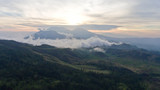 Aerial view of forest, mountains with fog, clouds at sunset on Bali,Indonesia. Tropical rainforest, trees, jungle in mountains. Fog over the jungle. Travel concept.