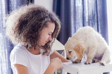 Teenager girl with a small golden retriever