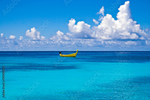 A distinctive yellow long-tail boat floating on the turquoise water at Ter Bay on Racha Island, Phuket, Thailand.