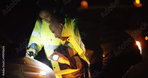 4k, Two mechanics fixing a car late a night with flash lights.