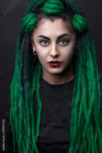 Pretty girl with green long dreadlocks. Black background. © dinachi