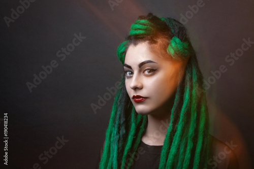 Pretty girl with green long dreadlocks. Black background. Mixed light. © dinachi