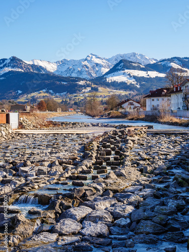 Fotobehang Bergrivier River in a village with winter mountain