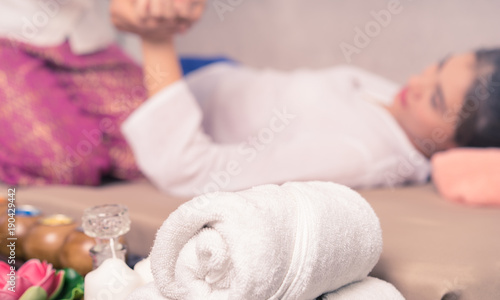Fotobehang Spa Woman is getting massaged with white towel and spa equipment on foreground