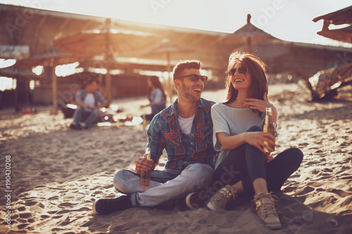 Happy young couple drinking beer and having fun at the beach during sunset