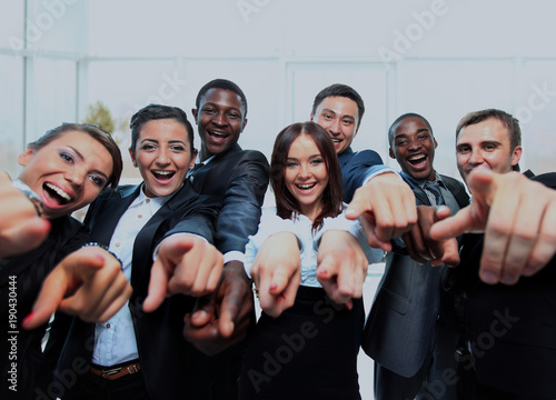 Portrait of excited young business people pointing at you.