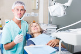 Dentist performing treatment to woman