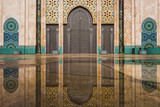 view of Hassan II mosque's big gate reflected on rain water - Casablanca - Morocco - 190451450